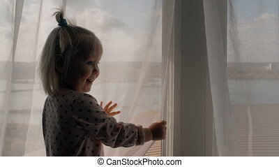 Child standing at window in room and looking delighted....