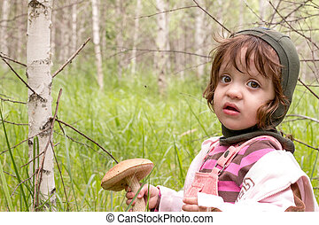 child standing in the forest with a mushroom