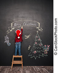 Child standing on stool and making Christmas drawing at ...