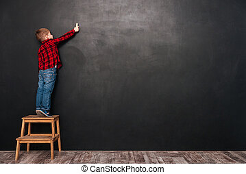 Child standing on stool over chalkboard and drawing at board