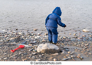 Child standing on the river bank