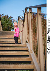 Child standing on wooden steps at beach looking down