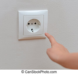 Child sticks his fingers in the socket. Dangerous situation at home.