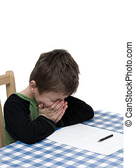 Child struggling with homework. Sitting at the table with a...