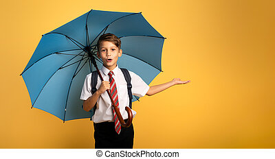 Child student with blue umbrella on yellow background. Amazed expression