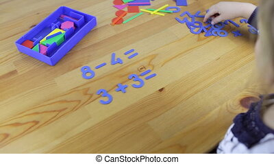 Small child studies arithmetic, solves examples