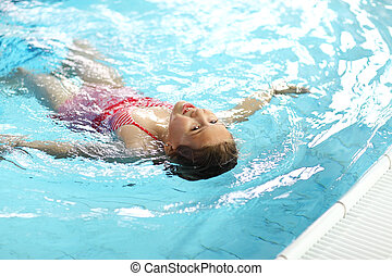 Child swimming backstroke in the pool