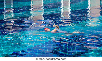 Child Swimming Freestyle in Swimming Pool