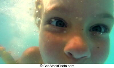 Child swimming in a pool, slow moti