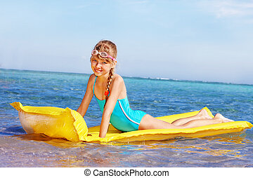 Child swimming inflatable beach mattress. - Little girl...
