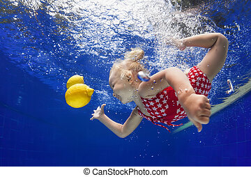 Child swimming underwater for yellow lemon in the blue pool