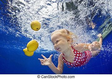 Child swimming underwater in blue pool for yellow lemon