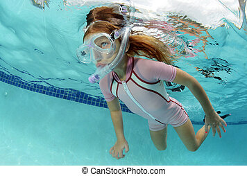 child swimming underwater in pool