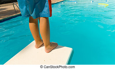 Child Swimming - Young boy standing on the end of a diving ...