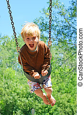Child Swinging at Park - a cute young child, with a big...