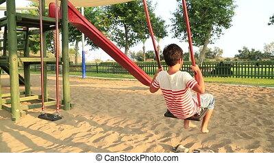 Child swinging at the playground - Elementary aged children...