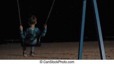 Child swinging on the beach at night