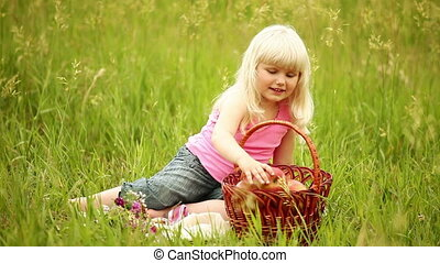 Child takes apple from the basket