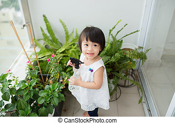 Child taking care of plants. Cute little girl watering first spring flowers