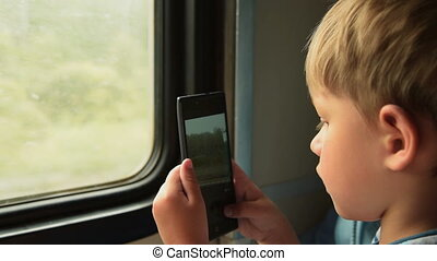 Child taking cellphone pictures in train