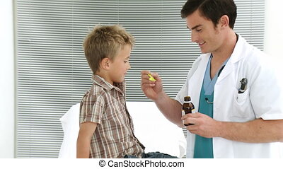 Child taking cough medicine in medical office