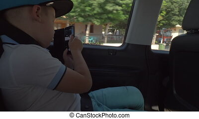 Child taking mobile photos of town during car ride