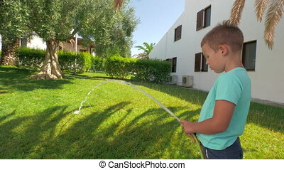 Child taking part in household duties and watering green...