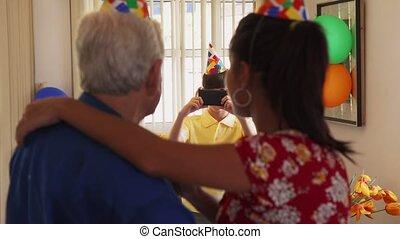 Child Taking Photo Of Happy Mom And Grandpa Dancing