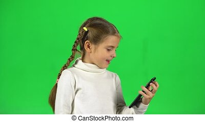 Child talking at video chatting on phone in studio against green screen