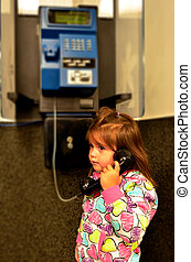 Child talks on a pay phone - Little girl talks on a pay...