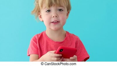 Child tapping cell phone screen, interest in modern...