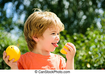 Child taste sour lemon. Eats the lemon boy, expression by the acid. Beautiful little kid boy with citrus on nature green background. Happiness emotions. Citrus fruit for health.