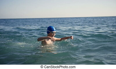 Child teen boy swims in the sea water.