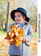 child the girl in a coat and a hat to stand with a bouquet of maple leaves