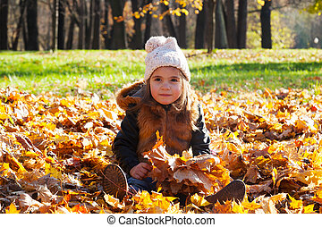 child the girl in a white cap sits among the fallen-down maple leaves