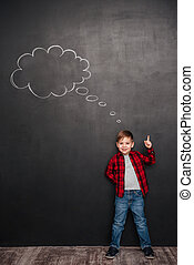 Child thinking with thought bubble on chalkboard while pointing up