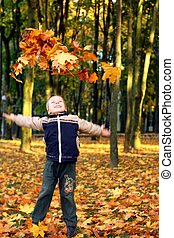 Child throwing autumn leaves