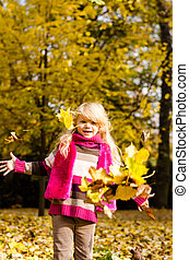 child throwing colorful autumn leaves