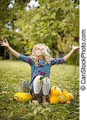 child throwing leaves in autumn time
