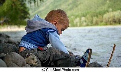 child throwing stones into the river - child have fun...