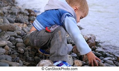 child throwing stones into the river slowmotion