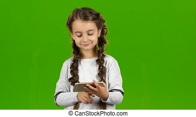 Child thumbs the photo on the phone. Green screen