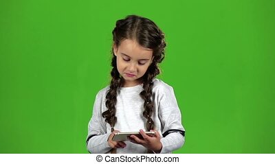 Child thumbs the photo on the phone. Green screen. Slow motion