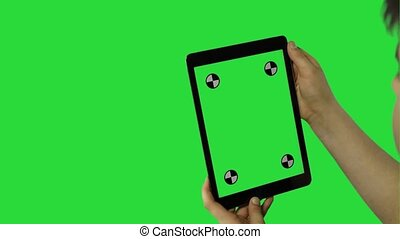 Child tilting to the left and right a tablet with green screen, back view