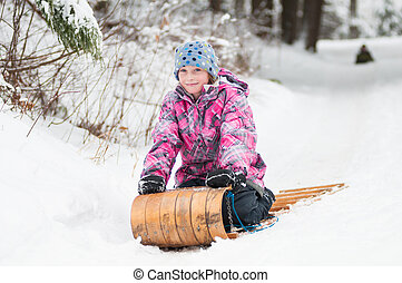 child tobogganing down a hill in winter