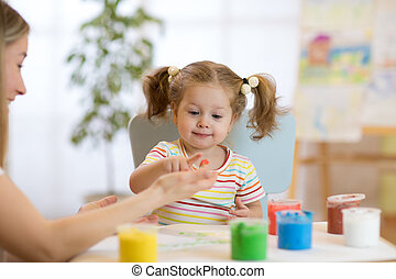 child toddler painting in nursery at home