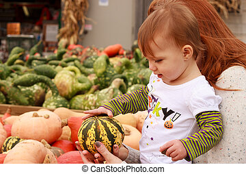 Child Touch Gourd - Mother showing daughter a gourd at a...