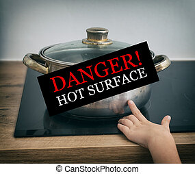 Child touches hot pan on the stove. Dangerous situation at...