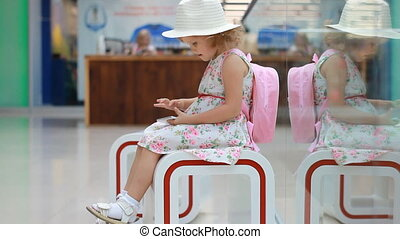 Child tourist in an airport terminal sitting in the waiting room playing with a mobile phone as they wait for their flight. Little girl uses a game application on a smartphone.