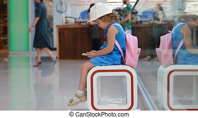Child tourist in an airport terminal sitting in the waiting room playing with a mobile phone as they wait for their flight. Little girl uses a game application on a smartphone